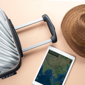 Flat lay grey suitcase with brown hat and map on gadget