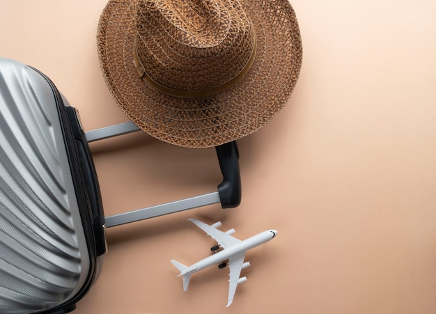 Flat lay grey suitcase with brown hat and mini airplane