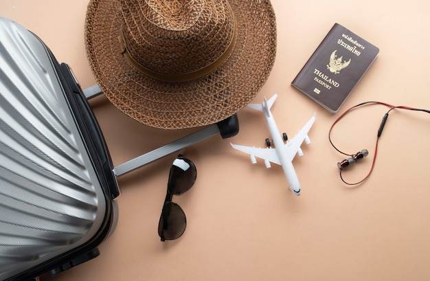 Flat lay grey suitcase with brown hat, mini airplane