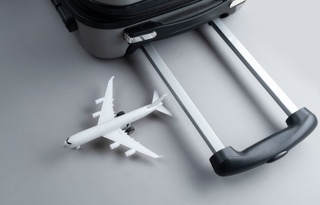 Flat lay grey suitcase with mini airplane on grey