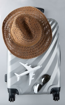 Flat lay grey suitcase with mini airplane and sun hat on grey background