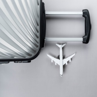 Flat lay grey suitcase with mini airplane. travel concept