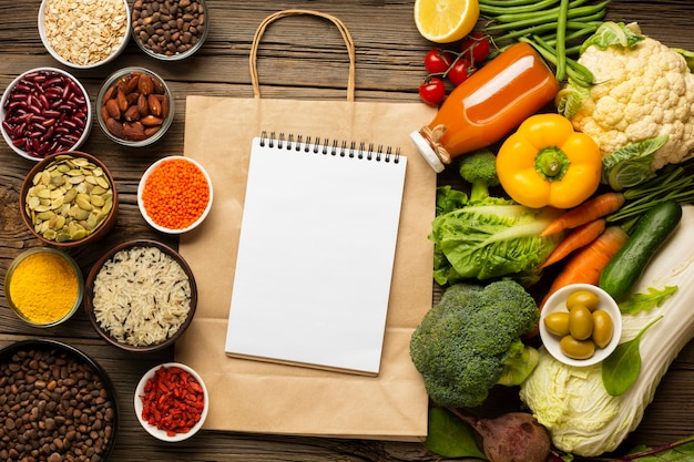 Flat lay of groceries with notebook mock-up Premium Photo
