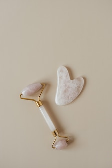 Flat lay of gua sha massage roller and stone scraper tool on neutral beige