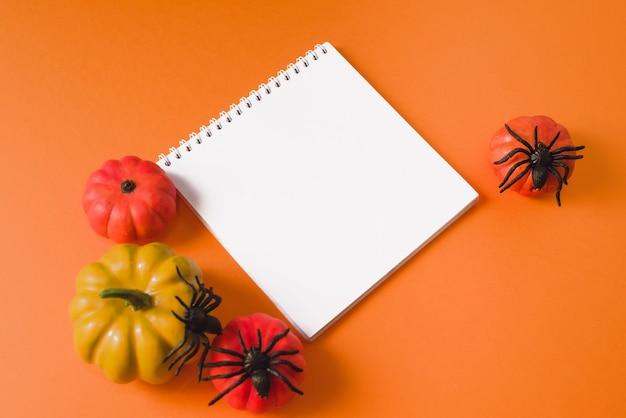 Плоская композиция на хэллоуин на оранжевом фоне с макетом. концепция хэллоуина. пустая рамка холста и украшение хэллоуина. хэллоуин макет плаката