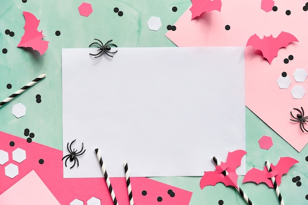 Flat lay, halloween party decor - hexagon confetti, paper drinking straws, flying bats and spiders.