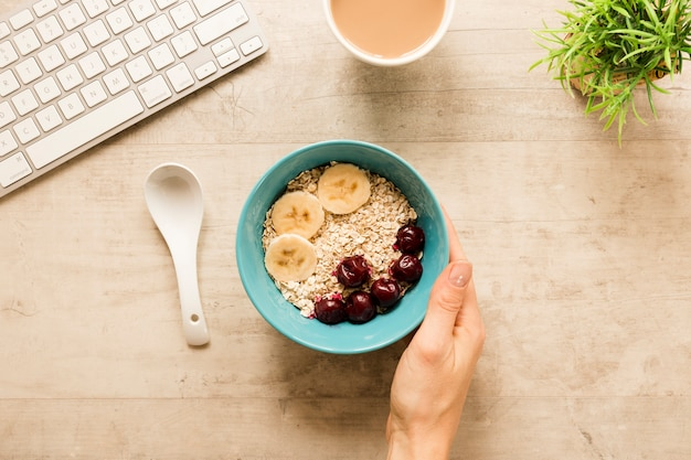 Flat lay hand holding bowl with oats and fruits