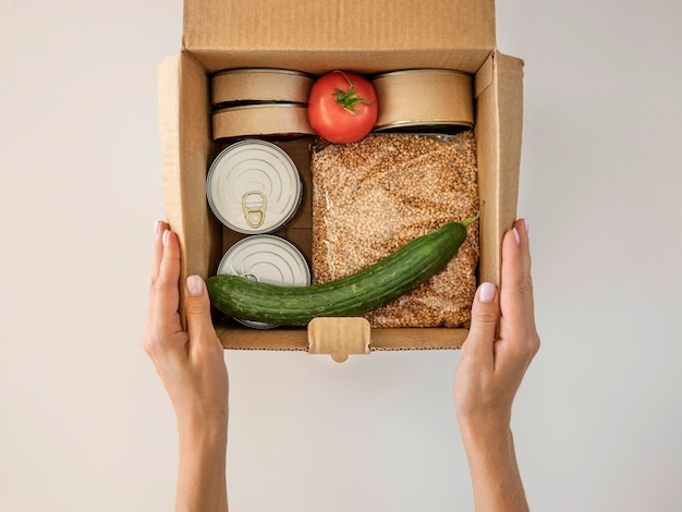Flat lay of hand holding box of food donation