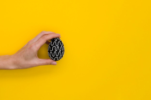 Disposizione piana della mano che tiene l'uovo di pasqua con lo spazio della copia e di progettazione