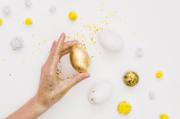 Flat lay of hand holding holding egg for easter with dandelions and glitter
