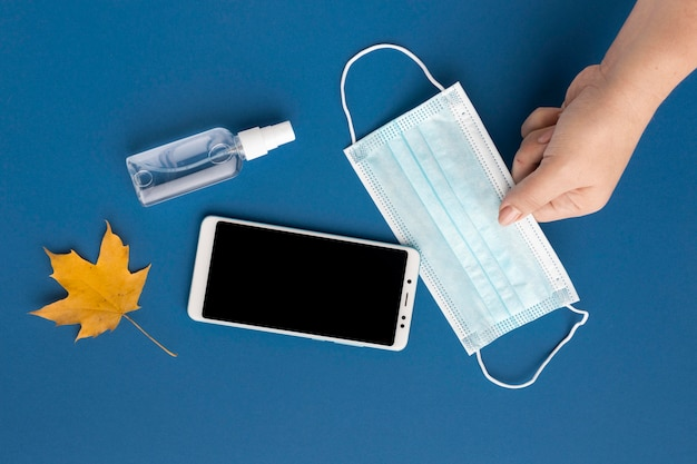 Flat lay of hand holding medical mask with smartphone and autumn leaf