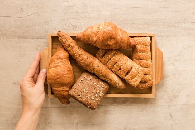 Flat lay hand holding mix of pastry in wooden box