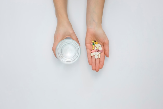 Flat lay of hand holding pills and glass of water