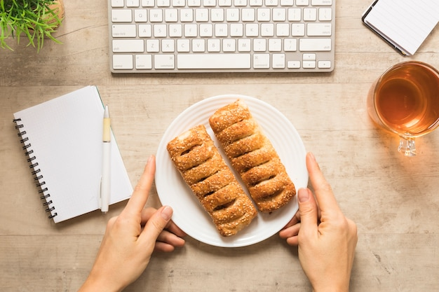 Flat lay hand holding plate of pastry with notebook