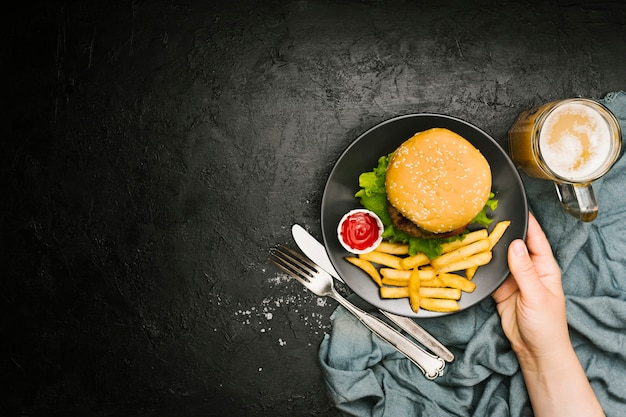 Flat-lay hand holding plate with burger and fries with copyspace
