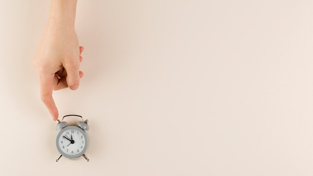 Flat lay of hand holding tiny clock with copy space