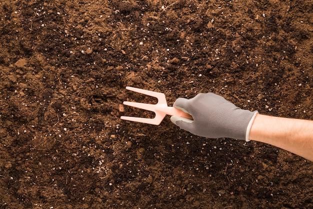 Flat lay of hand using rake on soil