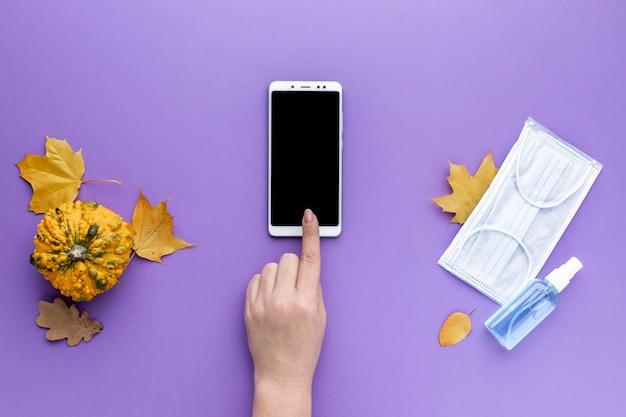 Lay piatto della mano utilizza lo smartphone con maschera medica e foglie di autunno