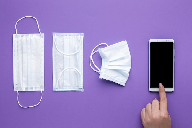 Flat lay of hand using smartphone with medical masks