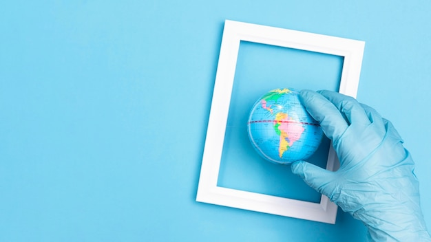 Flat lay of hand with surgical glove holding earth globe in frame