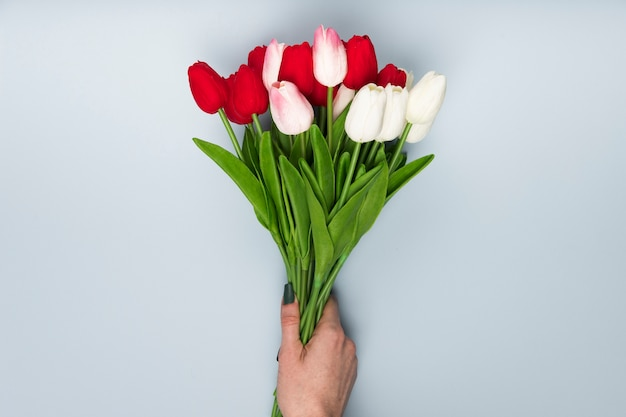 Flat lay hand with tulips bouquet