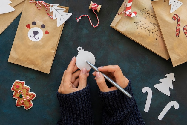 Flat lay of hands decorating christmas gift bags