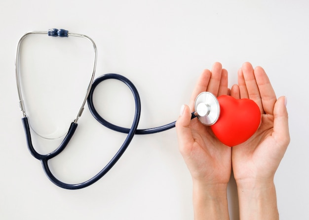 Flat lay of hands holding heart shape with stethoscope