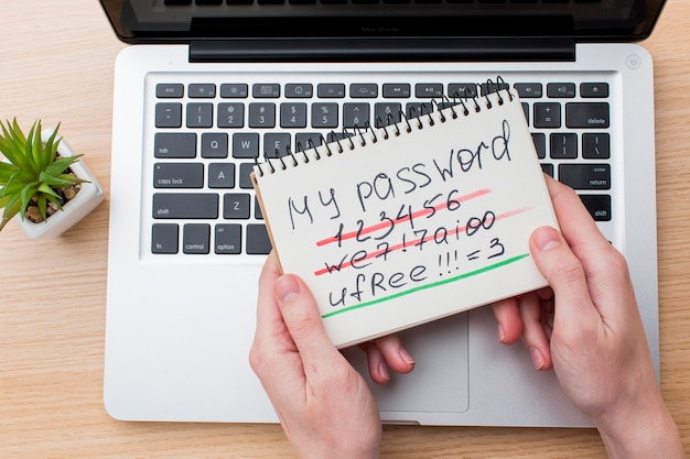 Flat lay of hands holding notebook with password and laptop