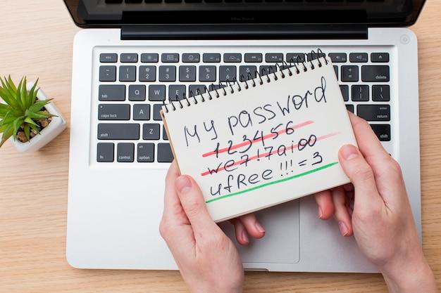 Disposizione piana delle mani che tengono taccuino con la password e il computer portatile