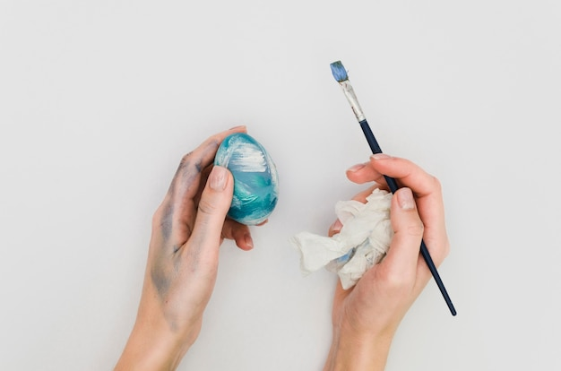 Flat lay of hands holding painted egg and brush