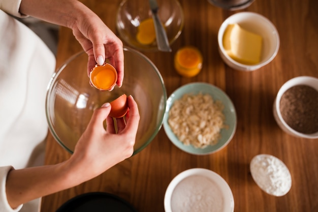 Flat lay of hands separating egg in bowl
