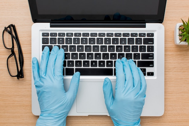 Flat lay of hands with gloves working on computer