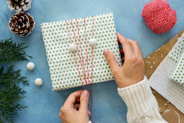 Flat lay of hands wrapping string around christmas gift