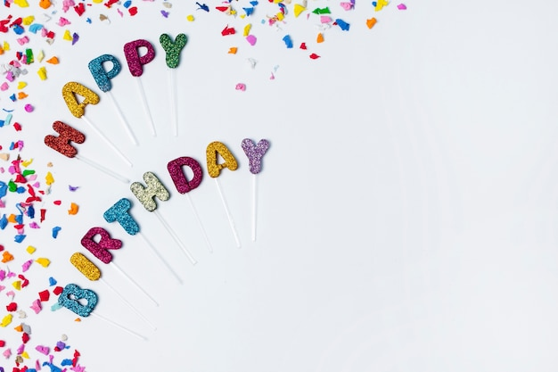 Flat lay happy birthday lettering on white background with copy space
