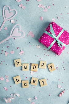 Flat lay of happy birthday wish in wooden letters and present