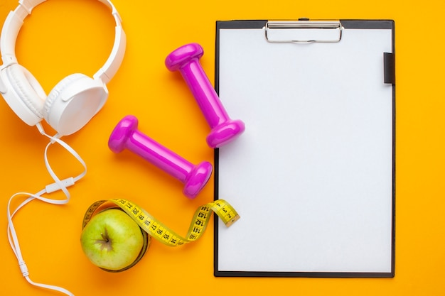 Flat lay headphones and clipboard on yellow background