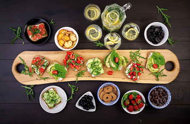 Flat lay of healthy vegetarian dinner table setting. sandwiches with tomato, cucumber, avocado, strawberry, herbs and olives, snacks. clean eating, vegan food