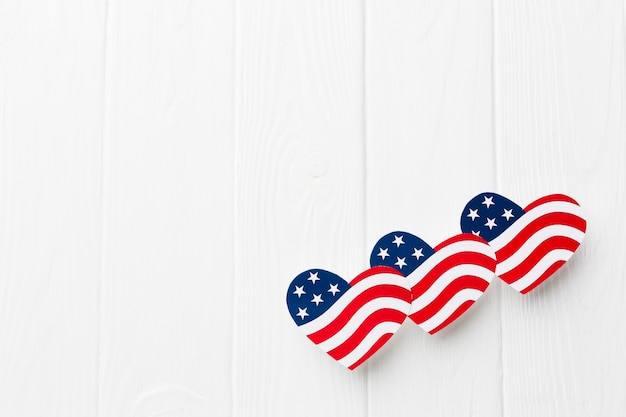 Flat lay of heart-shaped american flags with copy space for independence day