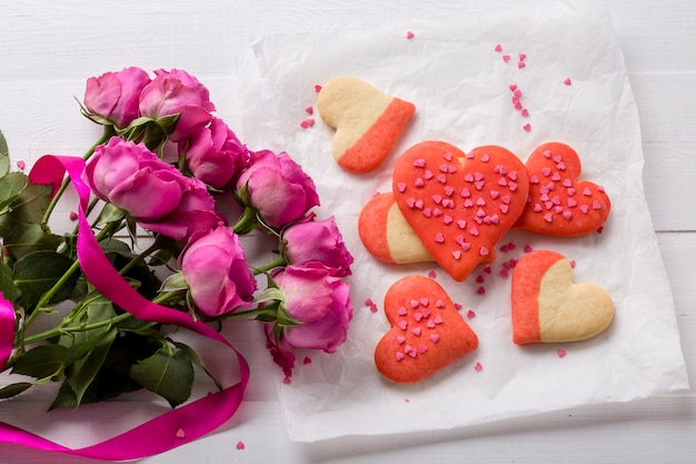 Flat lay of heart-shaped cookie with rose bouquet