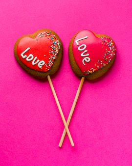 Flat lay of heart-shaped cookies on stick and pink background