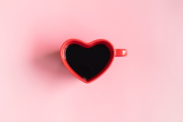 Flat lay of heart shaped cup of black coffee on a pink background with copy space.
