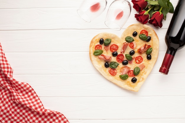 Flat lay heart shaped pizza on white background