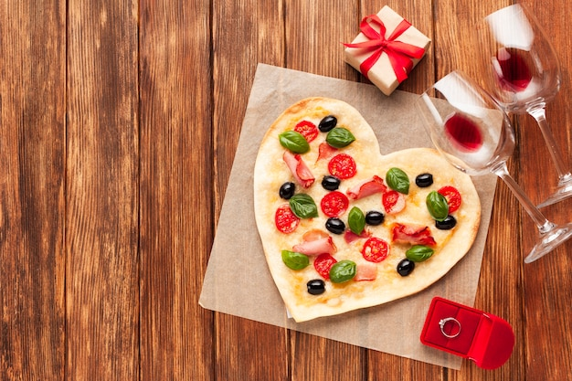 Flat lay heart shaped pizza with ring