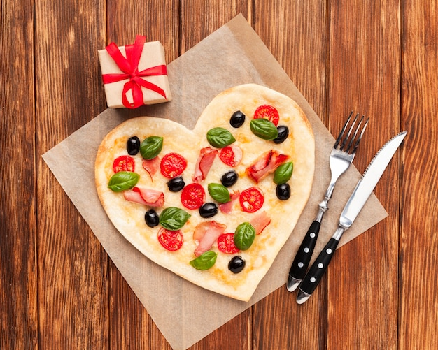 Flat lay heart shaped pizza with tableware