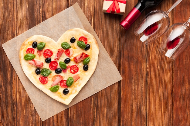 Flat lay heart shaped pizza with wine