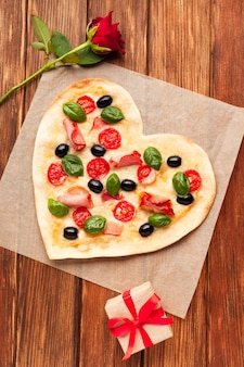 Flat lay heart shaped pizza on wooden table