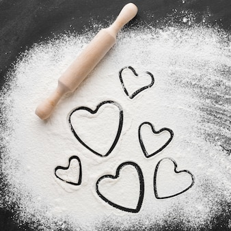 Flat lay of heart shapes in flour with rolling pin