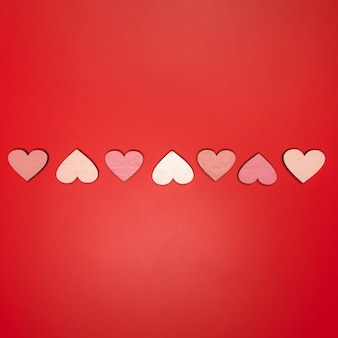Flat lay of hearts in line on red bright background.