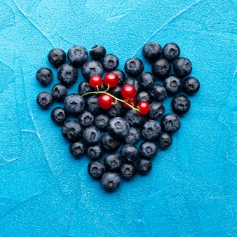 Flat-lay heartshaped blueberries and redcurrants