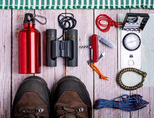 Flat lay of hiking equipment, essential tools on the wooden table